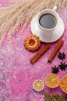 Bovenaanzicht kopje thee met koekje en kaneel op roze achtergrond kleur thee zoete koekje