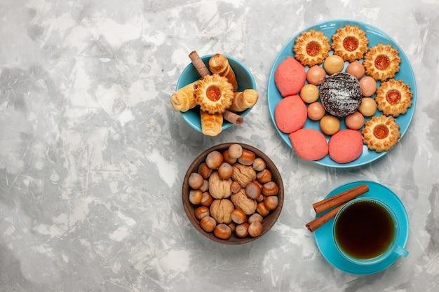 Bovenaanzicht kopje thee met koekjes, cakes en noten op witte ondergrond
