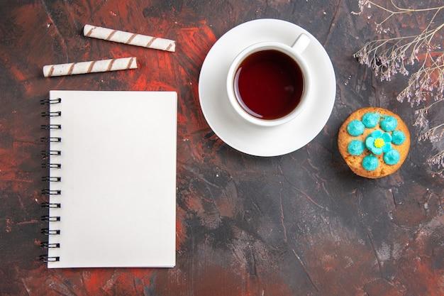 Bovenaanzicht kopje thee met koekjes en blocnote op donkere tafel koekje zoete koekjessuikergoed