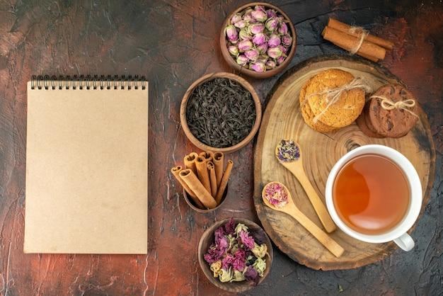 Bovenaanzicht kopje thee met koekjes en bloemen op donkere achtergrond smaak bloem kleur foto thee koffie