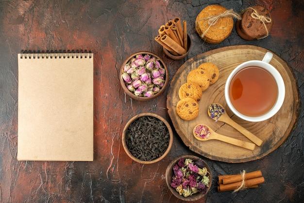 Bovenaanzicht kopje thee met koekjes en bloemen op donkere achtergrond smaak bloem kleur thee koffie foto