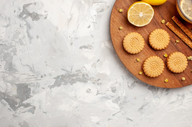 Bovenaanzicht kopje thee met koekjes en citroen op lichte witte ruimte