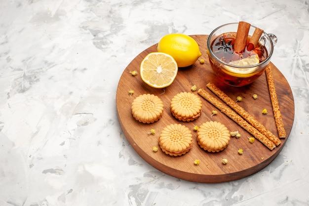Bovenaanzicht kopje thee met koekjes en citroen op witte ruimte