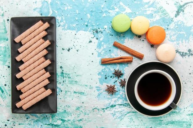 Bovenaanzicht kopje thee met koekjes en franse macarons op lichtblauw oppervlak
