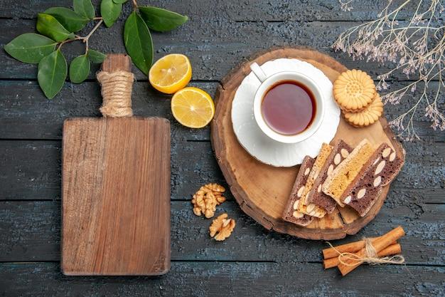 Bovenaanzicht kopje thee met koekjes en gebak op donkere tafel zoete koektaartsuiker
