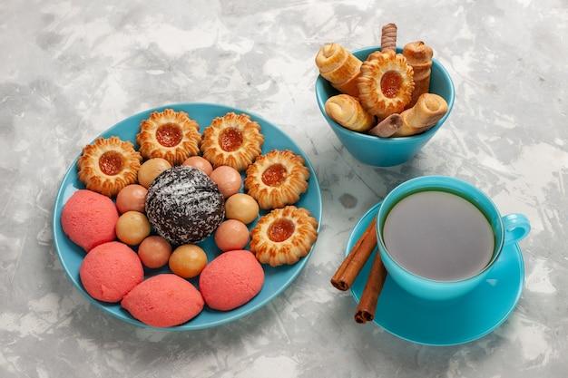 Bovenaanzicht kopje thee met koekjes en gebak op witte ondergrond