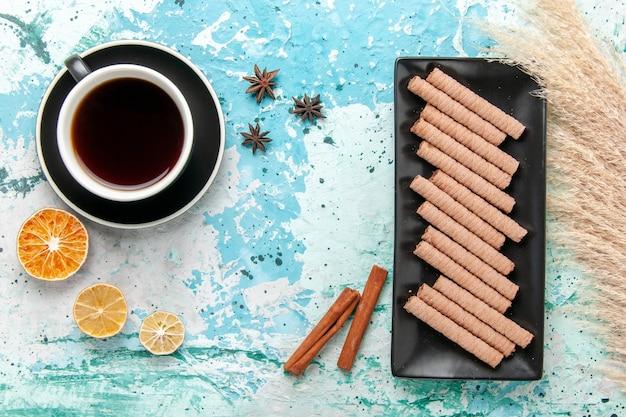 Bovenaanzicht kopje thee met koekjes en kaneel op blauwe ondergrond