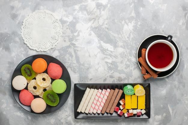 Bovenaanzicht kopje thee met koekjes en kleine gekleurde taarten op witte ondergrond