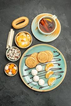 Bovenaanzicht kopje thee met koekjes en snoepjes op de grijze tafel cookie cake biscuit thee