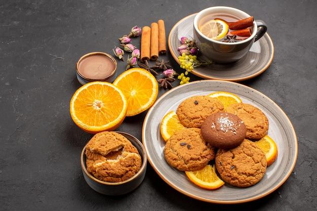 Bovenaanzicht kopje thee met koekjes en vers gesneden sinaasappels op donkere oppervlakte thee suiker fruitkoekje zoet koekje