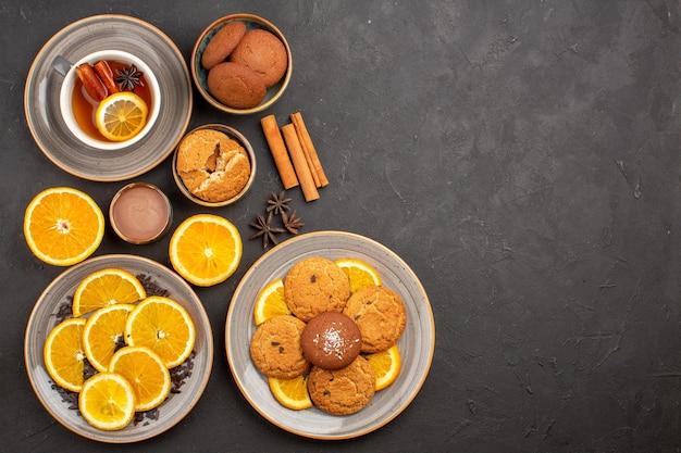 Bovenaanzicht kopje thee met koekjes en vers gesneden sinaasappels op het donkere oppervlak zoete thee fruitkoekje