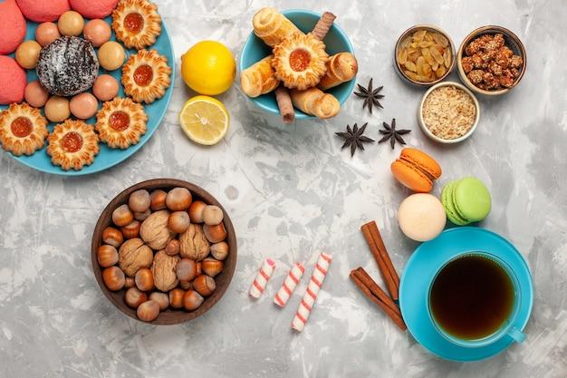 Bovenaanzicht kopje thee met koekjes, noten en roze taarten op witte ondergrond