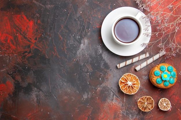 Bovenaanzicht kopje thee met koekjes op de donkere tafel