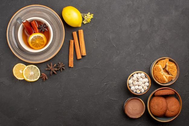 Bovenaanzicht kopje thee met koekjes op donkere oppervlakte thee fruitkoekje zoet