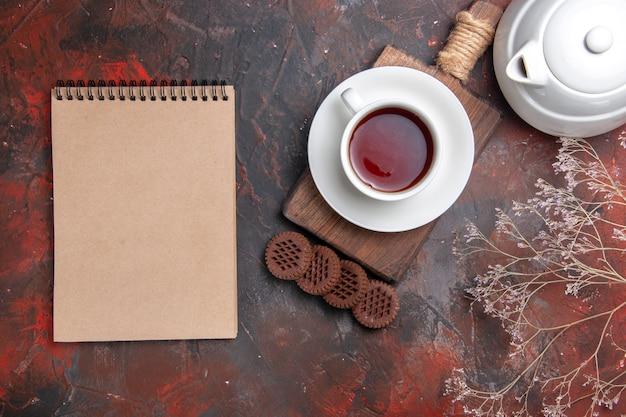 Bovenaanzicht kopje thee met koekjes op donkere vloer