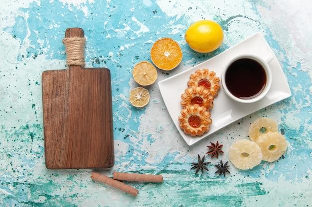 Bovenaanzicht kopje thee met koekjes op lichtblauw oppervlak