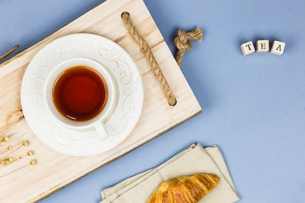 Bovenaanzicht kopje thee met letter dobbelstenen en tablet