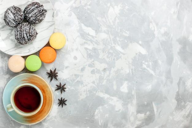 Bovenaanzicht kopje thee met macarons en chocoladetaart op wit bureau bakken cake biscuit suiker zoete taart