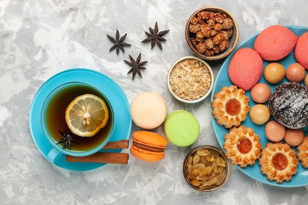Bovenaanzicht kopje thee met macarons en rozijnen op het witte bureau