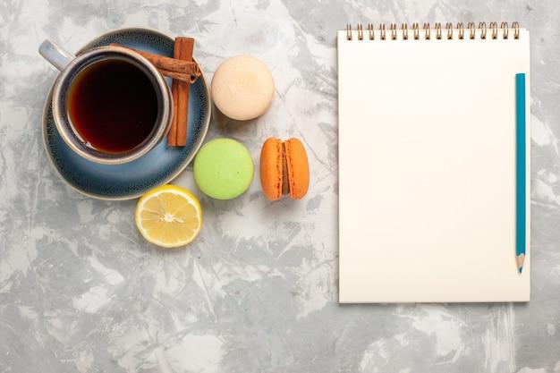 Bovenaanzicht kopje thee met macarons op witte ondergrond
