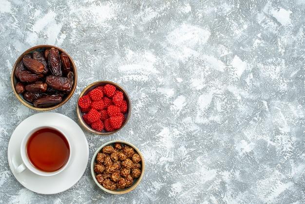 Bovenaanzicht kopje thee met noten en confitures op witte ruimte