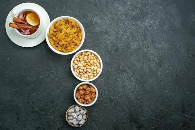 Bovenaanzicht kopje thee met noten en rozijnen op donkere oppervlakte snack noten zoete thee