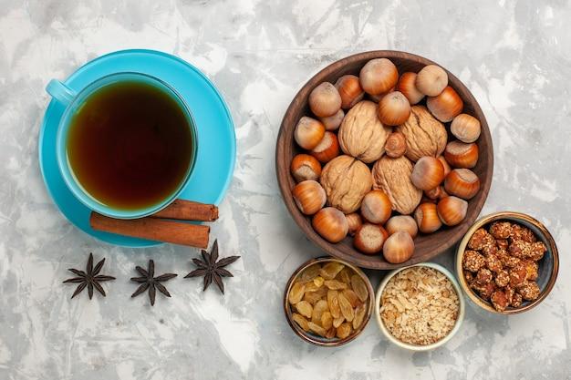 Bovenaanzicht kopje thee met noten en rozijnen op witte ondergrond