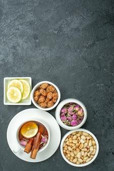 Bovenaanzicht kopje thee met noten en snoepjes op donkere oppervlakte theeceremonie notensnoepjes