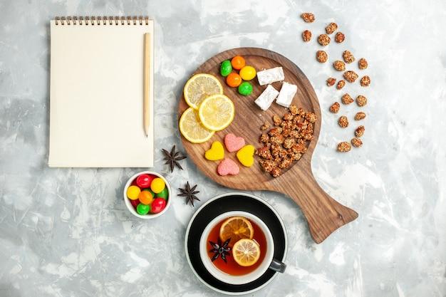 Bovenaanzicht kopje thee met noten en snoepjes op witte muur kandijsuiker zoete koekje cake thee