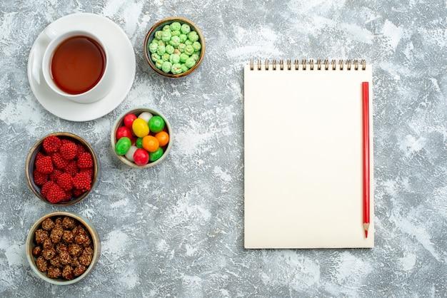 Bovenaanzicht kopje thee met noten en suikersuikergoed op een witte ruimte