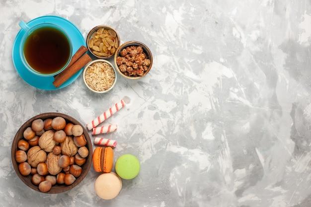 Bovenaanzicht kopje thee met noten kopje thee en rozijnen op witte ondergrond