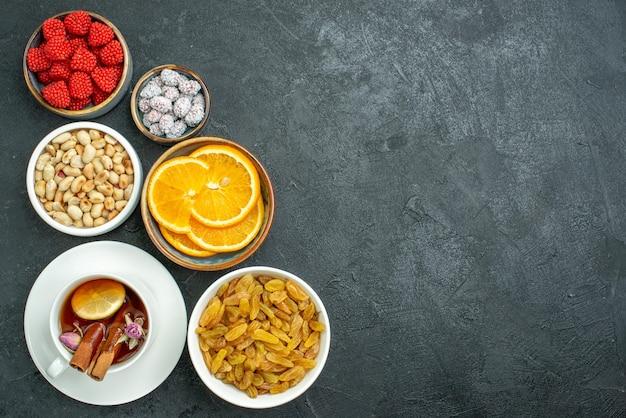 Bovenaanzicht kopje thee met noten, rozijnen en confitures op de donkere thee-notensnack