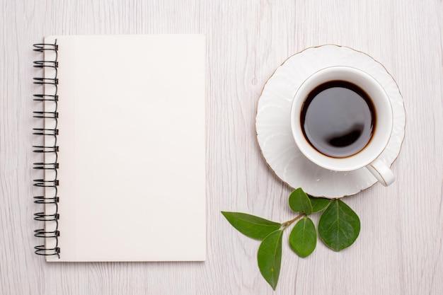 Bovenaanzicht kopje thee met notitieblok op witte bureau suiker thee koekjes zoete biscuit