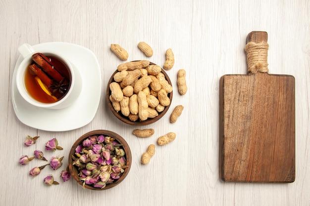 Bovenaanzicht kopje thee met pinda's en bloemen op witte bureaunoot thee bloemsmaak snack