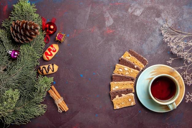 Bovenaanzicht kopje thee met plakjes cake en koekjes op donkere ruimte