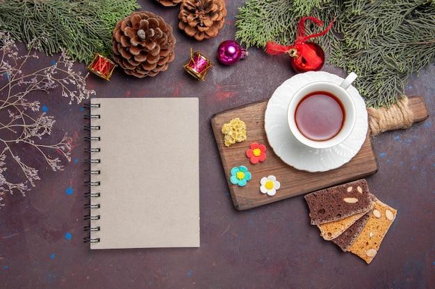 Bovenaanzicht kopje thee met plakjes cake op de donkere ruimte
