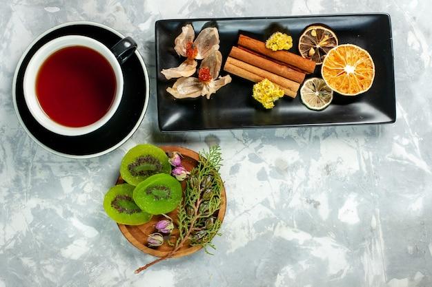Bovenaanzicht kopje thee met plakjes kiwi en kaneel op witte muur thee drinken bloem citroen