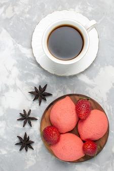 Bovenaanzicht kopje thee met roze peperkoek op wit