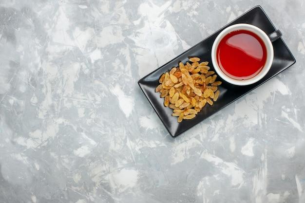 Bovenaanzicht kopje thee met rozijnen op witte ondergrond