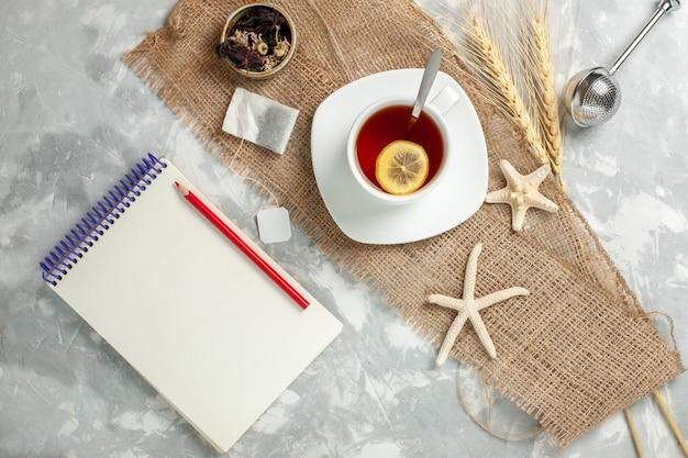 Bovenaanzicht kopje thee met schijfje citroen op wit bureau thee drinken fruit citroen