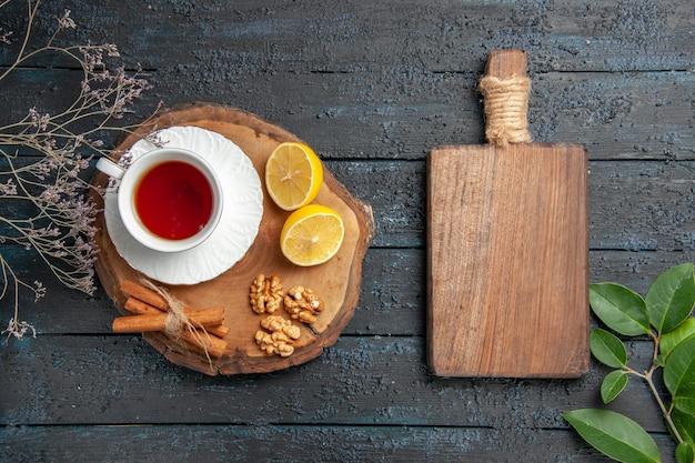 Bovenaanzicht kopje thee met schijfjes citroen op donkere tafel