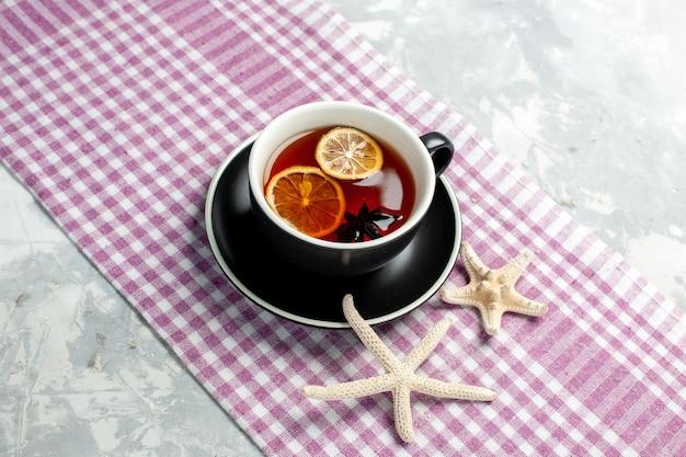 Bovenaanzicht kopje thee met schijfjes citroen op lichte ondergrond drinken theekopje