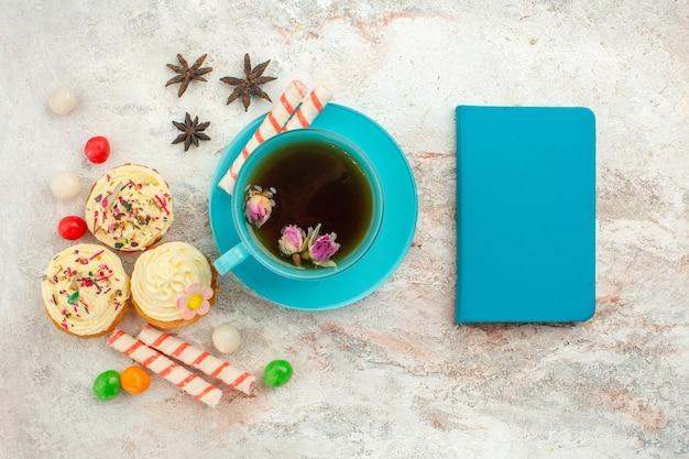 Bovenaanzicht kopje thee met snoep en gebak op witte oppervlakte thee dessert biscuit cake pie