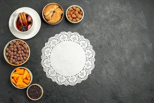 Bovenaanzicht kopje thee met snoep en noten op donkergrijs oppervlak thee drinken snoep