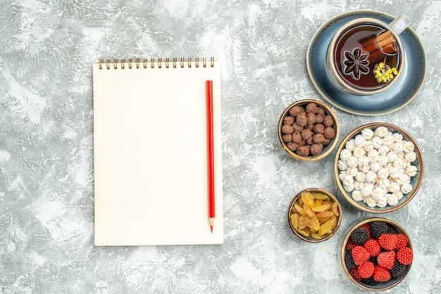 Bovenaanzicht kopje thee met snoep en notitieblok op witruimte