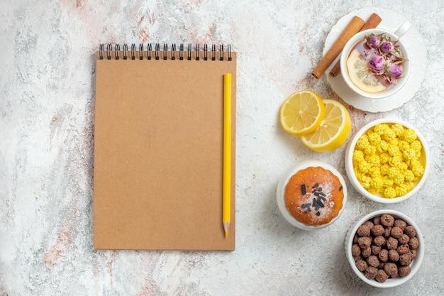 Bovenaanzicht kopje thee met snoep en schijfjes citroen op lichte witte ruimte