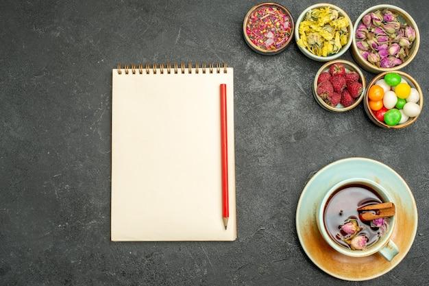 Bovenaanzicht kopje thee met snoepjes en bloemen op de donkere ruimte