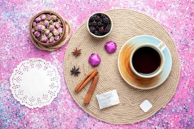 Bovenaanzicht kopje thee met snoepjes en kaneel op roze bureau.