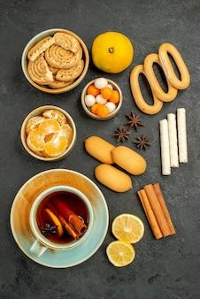 Bovenaanzicht kopje thee met snoepjes, koekjes en fruit op de grijze tafel thee zoete koekje