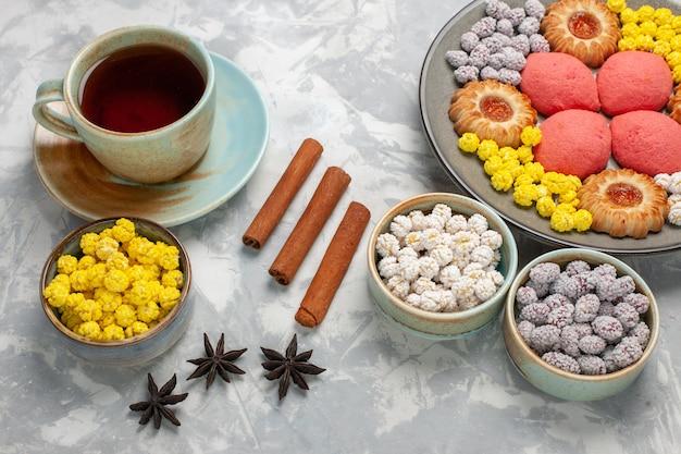 Bovenaanzicht kopje thee met snoepjes, koekjes en gebak op witte ondergrond